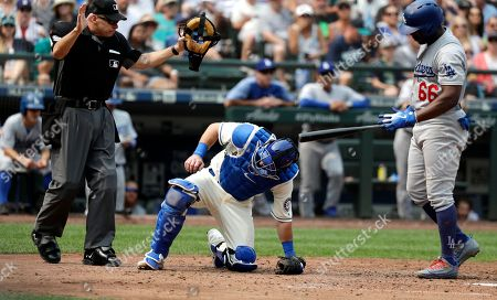 Seattle Mariners catcher Chris Herrmann, center, kneels after being hit by a ball as umpire Andy Fletcher, left, and Los Angeles Dodgers' Yasiel Puig look on during a baseball game, in Seattle