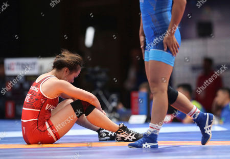 Thin Ha Phuong Phan, Sumiya Erdenechmig. Vietnam's Thin Ha Phuong Phan in red, reacts as she lost against Mongolia's Sumiya Erdenechmig during woman's freestyle 53kg. wrestling at the 18th Asian Games in Jakarta, Indonesia