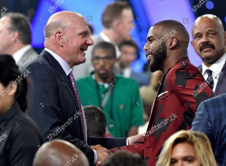 Steve Ballmer, owner of the Los Angeles Clippers, left, shakes hands with NBA player Chris Paul, of the Houston Rockets, in the audience at the NBA Awards, at the Barker Hangar in Santa Monica, Calif