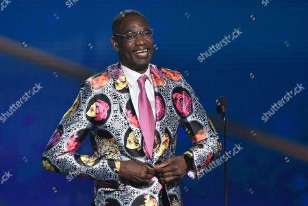Dikembe Mutombo puts on his Sager Strong award sport coat at the NBA Awards, at the Barker Hangar in Santa Monica, Calif