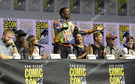 "Colman Domingo, standing, addresses the crowd at the ""Fear the Walking Dead"" panel on day two of Comic-Con International, in San Diego. Pictured from left are Robert Kirkman, Lennie James, Alycia Debnam-Carey, Danay Garcia, Jenna Elfman, Garret Dillahunt and Maggie Grace"