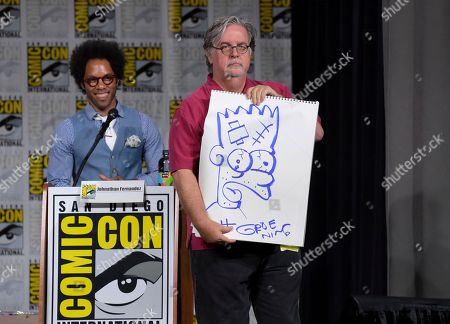 """Matt Groening, right, holds a signed drawing of Bart Simpson, as moderator Johnathan Fernandez looks on at a panel for """"The Simpsons"""" on day three of Comic-Con International, in San Diego"""