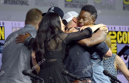 "Danai Gurira, right, and from left, Robert Kirkman and Angela Kang, hug Andrew Lincoln at a panel for ""The Walking Dead"" on day two of Comic-Con International, in San Diego"