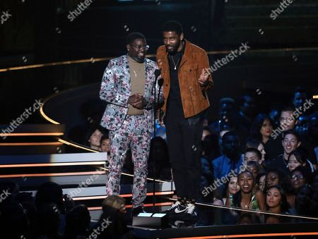 Lil Rel Howery, left, and Kyrie Irving present the most frightened performance award at the MTV Movie and TV Awards at the Barker Hangar in Santa Monica, Calif