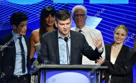 """Michael Schur, center, creator and executive producer of the television series """"The Good Place,"""" accepts the Outstanding Achievement in Comedy Award as cast members, from left, Manny Jacinto, Jameela Jamil, Ted Danson and Kristen Bell look on at the 34th annual TCA Awards during the 2018 Television Critics Association Summer Press Tour, in Beverly Hills, Calif"""