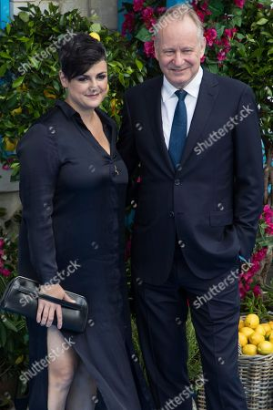 Megan Everett and Stellan Skarsgard pose for photographers upon arrival at the premiere of the film 'Mamma Mia! Here We Go Again', in London
