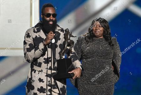 NBA player James Harden, of the Houston Rockets, left, accepts the most valuable player award as his mother, Monja Willis, looks on at the NBA Awards, at the Barker Hangar in Santa Monica, Calif