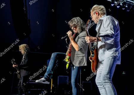 The English-American rock band Foreigner with rhythm guitarist Bruce Watson, vocalist Kelly Hansen, and lead guitarist Mick Jones performs at the Blue Hills Bank Pavilion, in Boston as part of The Juke Box Heroes Tour