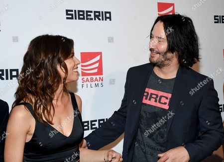 "Actors Ana Ularu, left, and Keanu Reeves greet each other at the premiere of ""Siberia"" at Metrograph, in New York"