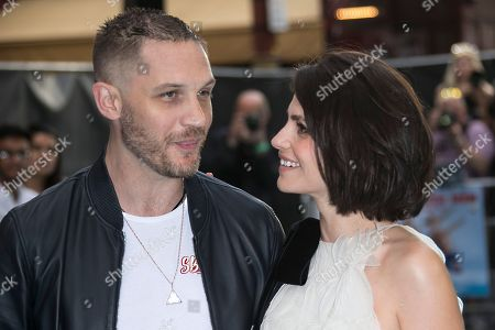 Actors Charlotte Riley, right, and Tom Hardy pose for photographers upon arrival at the premiere of the film Swimming With Men in central London