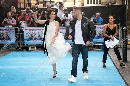 Actress Charlotte Riley, left, jokes with actor and husband Tom Hardy upon arrival at the premiere of the film Swimming With Men in central London