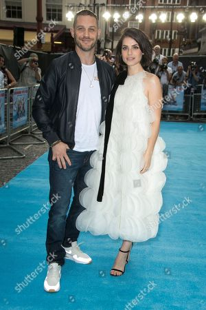 Actors Charlotte Riley and Tom Hardy pose for photographers upon arrival at the UK premiere Swimming With Men in central London