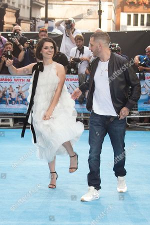 Actors Charlotte Riley aims a playful kick at Tom Hardy upon arrival at the UK premiere Swimming With Men in central London