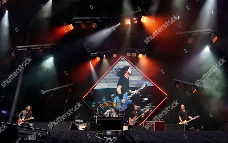 The American rock band Foo Fighters with front man and lead vocalist David Grohl, on video screen, performs at Fenway Park, in Boston. From left to right are guitarist Chris Shiflett, keyboardist Rami Jaffee, drummer Taylor Hawkins, bass player Nate Mendel, and guitarist Pat Smear