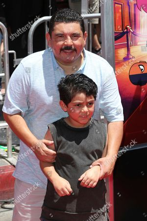 """Guillermo Rodriguez, back, and his son Benji Rodriguez arrive at the LA Premiere of """"Teen Titans Go! To the Movies"""" at the TCL Chinese Theatre, in Los Angeles"""