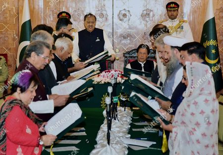 Stock Photo of In this photo released by Press Information Department, Pakistan's President Mamnoon Hussain, center left, administrates oath of office to federal ministers while Prime Minister Imran Khan, center right, looks on during a ceremony at a presidential palace in Islamabad, Pakistan, . Pakistan's 21-member Cabinet was sworn in Monday, a day after Prime Minister Imran Khan pledged to cut government spending, end corruption and repatriate public funds