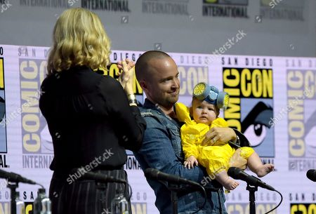 """Anna Gunn, from left, looks on as Aaron Paul holds his daughter Story Annabelle, dressed as his character Jesse Pinkman, at the """"Breaking Bad"""" 10th Anniversary panel on day one of Comic-Con International, in San Diego"""