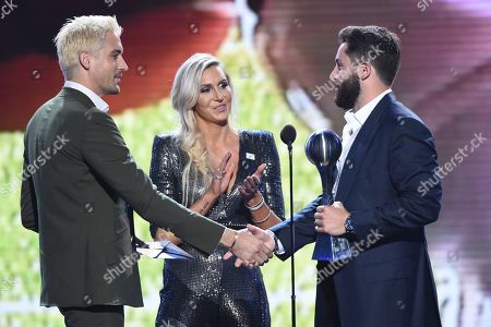 G-Eazy, from left, and Charlotte Flair present the award for best college athlete to NFL football player Baker Mayfield, of the Cleveland Brown for his time with Oklahoma at the ESPY to Awards at the Microsoft Theater, in Los Angeles