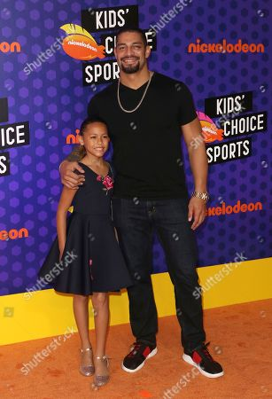 Roman Reigns, right, and Joelle Anoa'i arrives at the Kids' Choice Sports Awards at the Barker Hangar, in Santa Monica, Calif