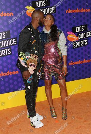 Host Chris Paul, left, kisses Jada Crawley at the Kids' Choice Sports Awards at the Barker Hangar, in Santa Monica, Calif