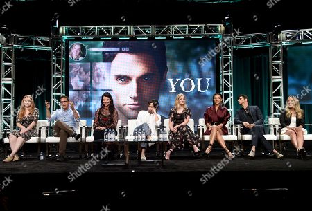 """Executive producer Sarah Schechter, from left, executive producer/co-creators Greg Berlanti and Sera Gamble, Penn Badgley, Elizabeth Lail, Shay Mitchell, John Stamos and author Caroline Kepnes participate in Lifetime's """"YOU"""" panel during the Television Critics Association Summer Press Tour at The Beverly Hilton hotel, in Beverly Hills, Calif"""
