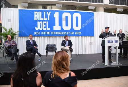Musician Billy Joel, right, speaks at a press conference to celebrate his 100th lifetime concert as actor Chazz Palminteri, left, New York Governor Andrew Cuomo and The Madison Square Garden Company executive chairman and CEO James L. Dolan at Madison Square Garden on in New York