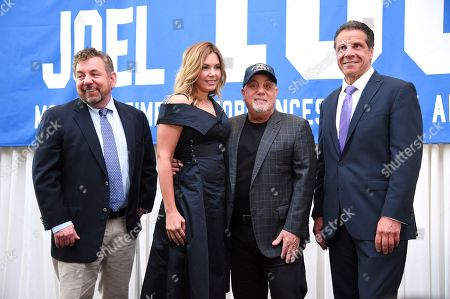 The Madison Square Garden Company executive chairman and CEO James L. Dolan, left, Billy Joel's wife Alexis Roderick, Billy Joel and New York Governor Andrew Cuomo pose together during a press conference to celebrate Billy Joel's 100th lifetime concert at Madison Square Garden on in New York