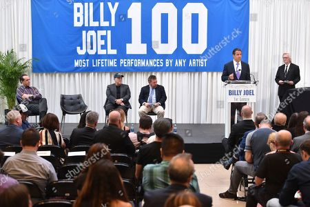 Musician Billy Joel, left, and The Madison Square Garden Company executive chairman and CEO James L. Dolan look on as New York Governor Andrew Cuomo speaks at a press conference to celebrate Billy Joel's 100th lifetime concert at Madison Square Garden on in New York