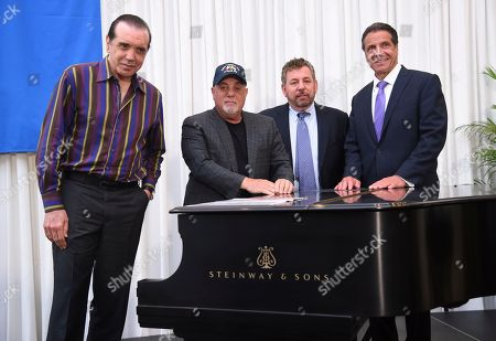 Actor Chazz Palminteri, from left, musician Billy Joel, The Madison Square Garden Company executive chairman and CEO James L. Dolan and New York Gov. Andrew Cuomo pose together with a piano during a press conference to celebrate Joel's 100th lifetime concert at Madison Square Garden on in New York