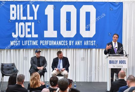 Musician Billy Joel, left, and The Madison Square Garden Company executive chairman and CEO James L. Dolan look on as New York Governor Andrew Cuomo, right, speaks at a press conference to celebrate Joel's 100th lifetime concert at Madison Square Garden on in New York
