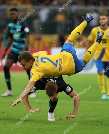 David Sauerland (top) of Eintracht Braunschweig in action against Berlin's Maximilian Mittelstaedt (bottom) during the German DFB Cup first round soccer match between Eintracht Braunschweig and Hertha BSC in Braunschweig, Germany, 20 August 2018.  (ATTENTION: The DFB prohibits the utilisation and publication of sequential pictures on the internet and other online media during the match (including half-time). ATTENTION: BLOCKING PERIOD! The DFB permits the further utilisation and publication of the pictures for mobile services (especially MMS) and for DVB-H and DMB only after the end of the match.)