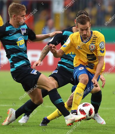 David Sauerland (R) of Eintracht Braunschweig in action against Berlin's Maximilian Mittelstaedt (L) during the German DFB Cup first round soccer match between Eintracht Braunschweig and Hertha BSC in Braunschweig, Germany, 20 August 2018.  (ATTENTION: The DFB prohibits the utilisation and publication of sequential pictures on the internet and other online media during the match (including half-time). ATTENTION: BLOCKING PERIOD! The DFB permits the further utilisation and publication of the pictures for mobile services (especially MMS) and for DVB-H and DMB only after the end of the match.)