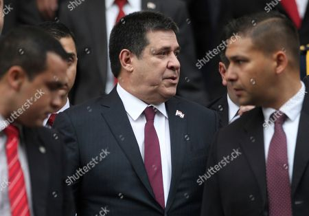 Flanked by his security detail, Paraguay's outgoing President Horacio Cartes exits Congress leaving the presidential inauguration ceremony before it finished, in Asuncion, Paraguay. Cartes has been unhappy that incoming President Abdo Benitez has failed to back his effort to take an elected seat in the Senate