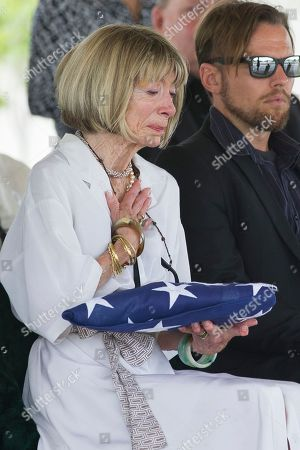 Brenda Smiley holds the American flag during a service for her husband longtime Associated Press journalist Richard Pyle at Arlington National Cemetery, in Arlington, Va. Pyle retired in 2009 after 49 years with the AP, a career in which he documented some of the most historic moments of the 20th century and beyond. During the Vietnam War, Pyle served as chief of AP's Pulitzer Prize-winning Saigon bureau. He later covered the post-Watergate presidential transition from Richard Nixon to Gerald Ford