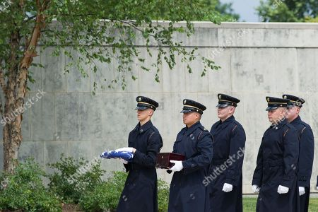 Members of the 3rd Infantry Regiment, The Old Guard, carry the remains of longtime Associated Press journalist Richard Pyle as he is interned with military honors at Arlington National Cemetery, in Arlington, Va. Pyle retired in 2009 after 49 years with the AP, a career in which he documented some of the most historic moments of the 20th century and beyond. During the Vietnam War, Pyle served as chief of AP's Pulitzer Prize-winning Saigon bureau. He later covered the post-Watergate presidential transition from Richard Nixon to Gerald Ford