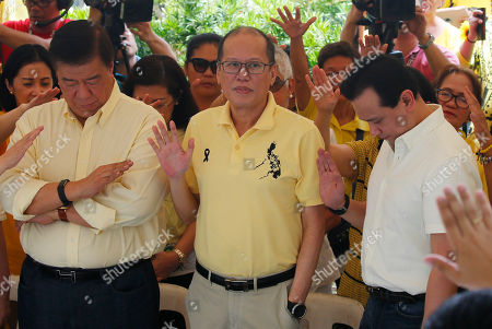 """Benigno Aquino III, Franklinn Drilon, Antonio Trillanes IV. Former President Benigno Aquino III, center, is prayed over by supporters as he leads the commemoration of the August 21, 1983 Manila International Airport assassination of his father, opposition Senator Benigno Aquino Jr. at the Manila Memorial Park in suburban Paranaque east of Manila, Philippines . Aquino Jr.'s assassination sparked series of protest that eventually toppled the late dictator Ferdinand Marcos from 20-year-rule and helped install his widow Corazon """"Cory"""" Aquino to the presidency via People Power revolt. Flanking Aquino III are opposition Senators Franklinn Drilon, left, and Antonio Trillanes IV"""