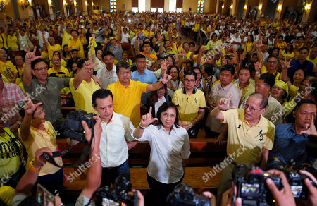 """Benigno Aquino III, Leni Robredo, Antonio Trillanes IV. Former President Benigno Aquino III, second from right, Vice President Leni Robredo, center, and Senator Antonio Trillanes IV, second from left, flash the """"L"""" sign, meaning """"Fight!"""" following a Mass in commemoration of the Aug. 21, 1983 Manila International Airport assassination of Aquino III's father, opposition Senator Benigno Aquino Jr. at Sto. Domingo church in suburban Quezon city, north of Manila, Philippines . Aquino Jr.'s assassination sparked series of protests that eventually toppled the late dictator Ferdinand Marcos from 20-year-rule and helped install his widow Corazon """"Cory"""" Aquino to the presidency via People Power revolt"""