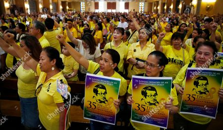 """Supporters display posters of assassinated opposition Senator Benigno Aquino Jr. while singing a nationalist song following a Mass in commemoration of the August 21, 1983 Manila International Airport assassination of Aquino Jr. at Sto. Domingo church in suburban Quezon city, north of Manila, Philippines . Aquino Jr.'s assassination sparked series of protests that eventually toppled the late dictator Ferdinand Marcos from 20-year-rule and helped install his widow Corazon """"Cory"""" Aquino to the presidency via People Power revolt"""