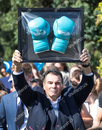 Paddy Doherty carries boxing gloves behind the coffin at the funeral of traveller Mikey Connors in Epsom cemetery.