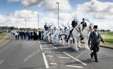 Paddy Doherty walks next to the horse drawn hearse carrying the coffin of his nephew Mikey Connors at Epsom cemetery.