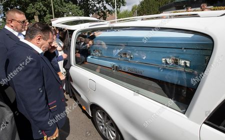 Family members, including Paddy Doherty (L), mourn as the coffin of his nephew Mikey Connors is carried from St Michaels Church in Ashstead.