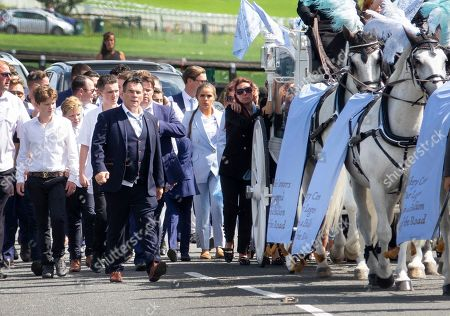 Paddy Doherty (blue suit) walks next to the horse drawn hearse carrying the coffin of his nephew Mikey Connors at Epsom cemetery.