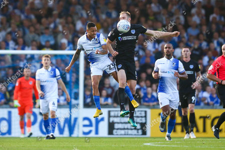Kyle Bennett of Bristol Rovers and Matthew Clarke of Portsmouth contend for the aerial ball