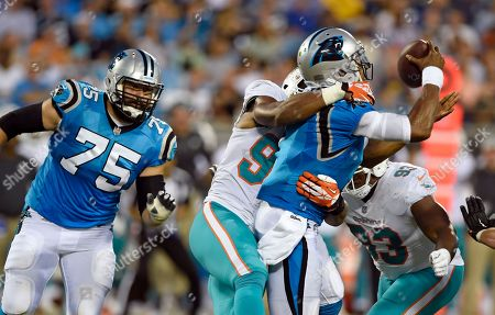 Carolina Panthers' Matt Kalil, left, runs in as Cam Newton, second from right, is sacked by Miami Dolphins' Robert Quinn, second from left, and Akeem Spence, right, in the first half of a preseason NFL football game in Charlotte, N.C. Kalil becomes Carolina's third starting offensive lineman to go down with a knee injury. Right tackle Daryl Williams and left guard Amini Silatolu also are out with injuries