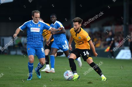 Josh Sheehan of Newport County looks for a way past David Vaughan of Notts County.