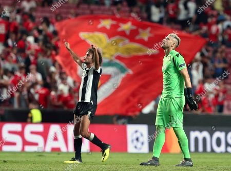 PAOK's Amr Warda, left, and PAOK goalkeeper Alexandros Paschalakis salute fans at the end of the Champions League playoffs, first leg, soccer match between Benfica and PAOK at the Luz stadium in Lisbon