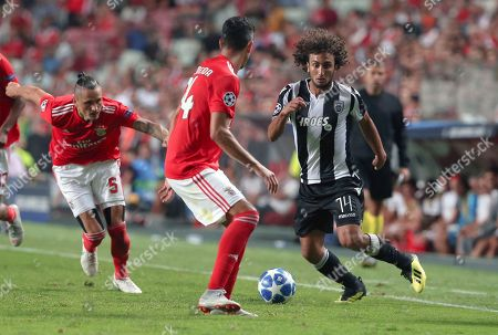 PAOK's Amr Warda, right, challenges for the ball with Benfica's Andre Almeida during the Champions League playoffs, first leg, soccer match between Benfica and PAOK at the Luz stadium in Lisbon