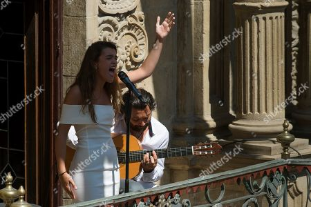 Spanish singer Amaia Romero (L) performs accompanied by Spanish guitar player Pepe Habichuela (R) at a balcony in downtown Pamplona, norther Spain, 21 August 2018, on occasion of a tribute to Spanish guitar player Carlos Itoiz at the Flamenco On Fire Festival.