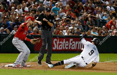 A wild throw by Los Angeles Angels relief pitcher Cam Bedrosian gets past Angels third baseman Taylor Ward, left, as Arizona Diamondbacks center fielder Jon Jay (9) slides safely into third base as umpire Andy Fletcher, middle, looks on during the ninth inning of a baseball game, in Phoenix. The Diamondbacks defeated the Angels 5-4