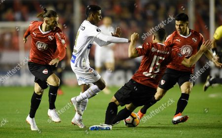 Rodrygo of Brazil's Santos, center, fights for the ball with Diego Rodriguez, right, and Gaston Silva, left, of Argentina's Independiente, during a Copa Libertadores soccer match in Buenos Aires, Argentina